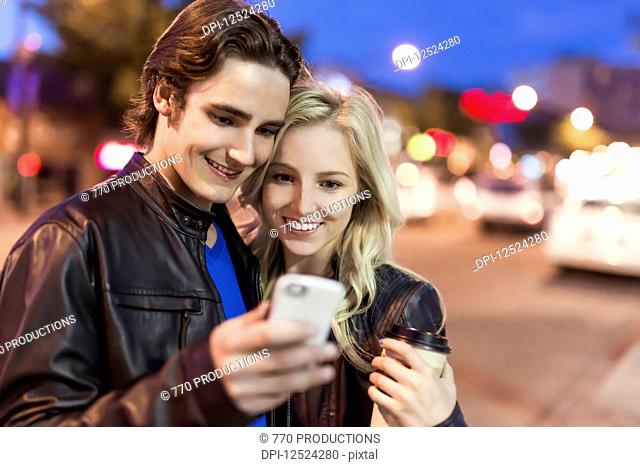 A young couple use a smart phone along a street at dusk; Edmonton, Alberta, Canada