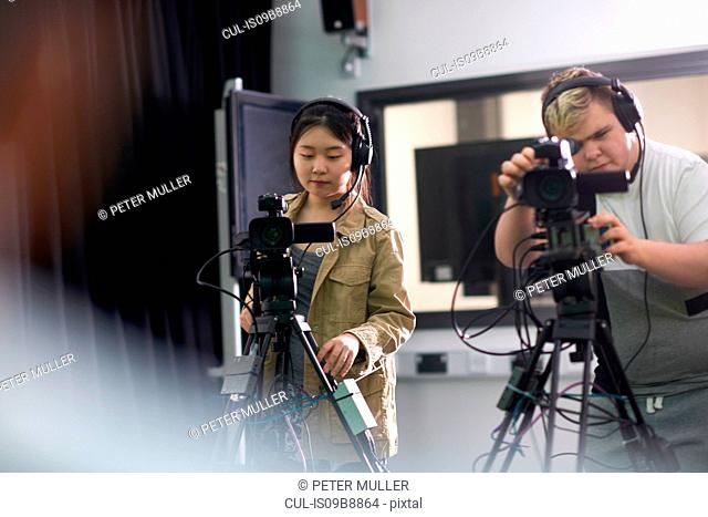 Over shoulder view of college students filming in TV studio