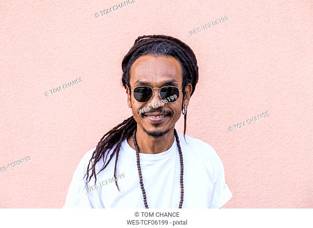 Portrait of smiling mature man with dreadlocks and sunglasses