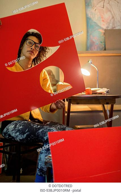 Artist cutting out red cardboard