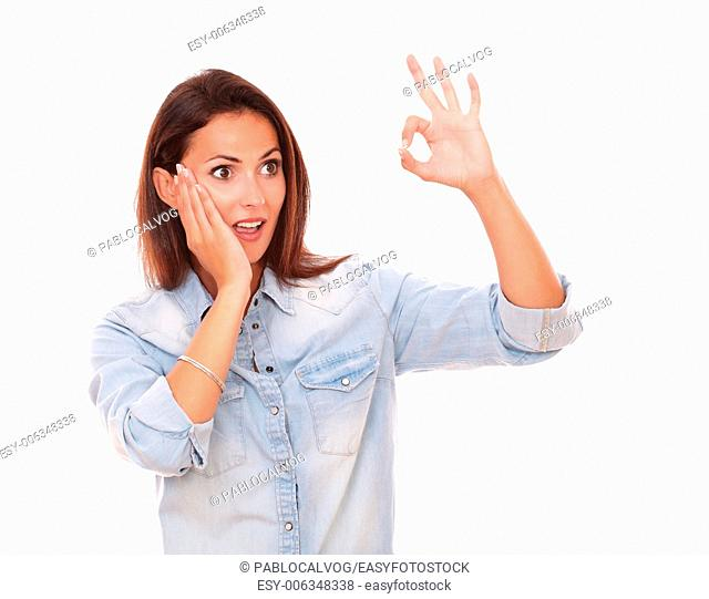Portrait of surprised single lady with ok sign looking at her left while standing on isolated studio - copyspace