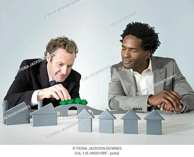 Two business men play with a train
