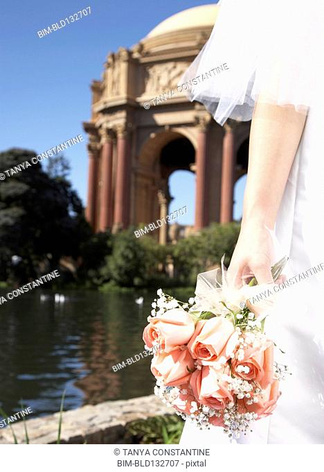 Chinese bride holding bouquet in urban park, San Francisco, California, United States
