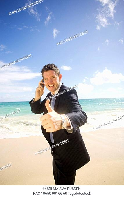 Hawaii, Oahu, young man at the beach in business attire giving 'thumbs-up'