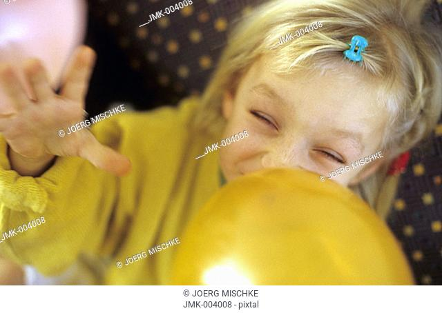 A little girl, 5-10 years old, inflating a balloon