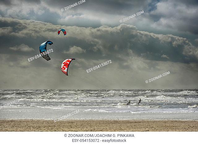 3 Kitesurfer an der holländischen Nordseeküste bei stürmischer See 3 man kitesurfing the waves of the stormy North Sea at the dutch coast
