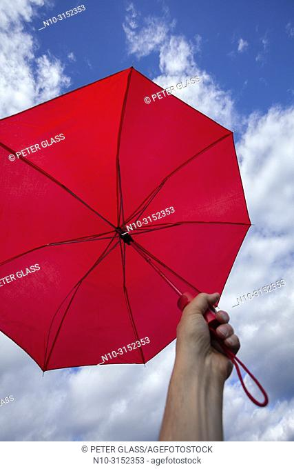 Man's hand holding a red umbrella against a cloudy sky