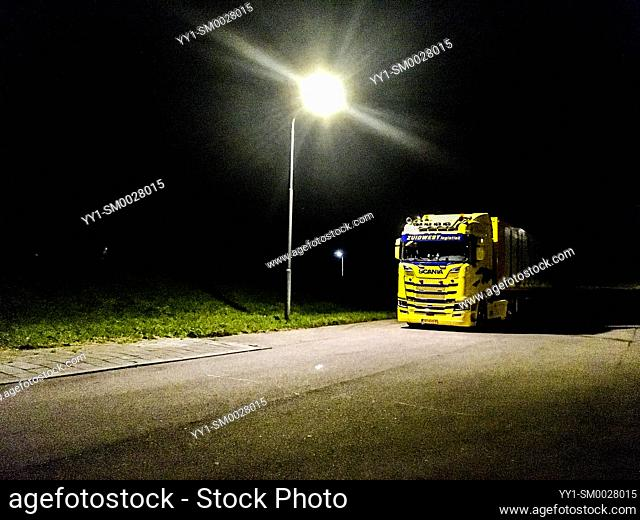 Yrseke, Netherlands. Yellow truck and freighter parked overnight on a scarsly illuminated parking lot