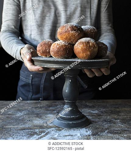 Crop human holding tray with set of fresh beignets with powdered sugar