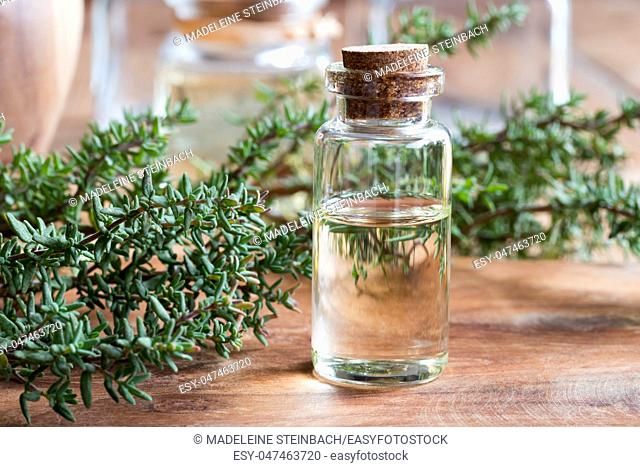 A bottle of thyme essential oil with fresh thyme twigs on a wooden table