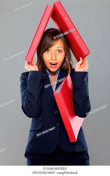 Businesswoman holding folders isolated on gray background expressing emotion