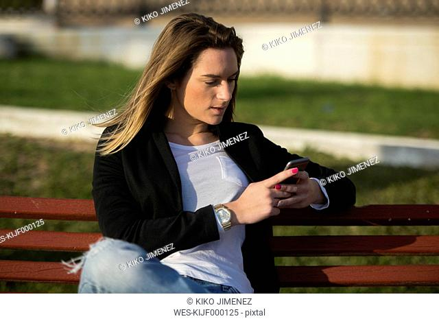 Woman sitting on a bench looking at smartphone