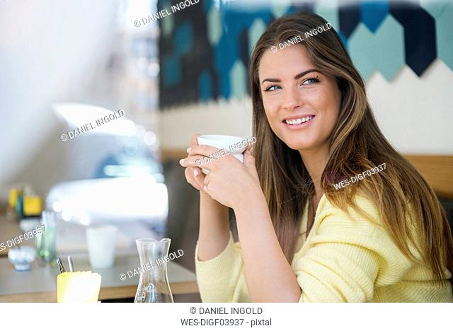 Smiling young woman in a cafe holding cup of coffee