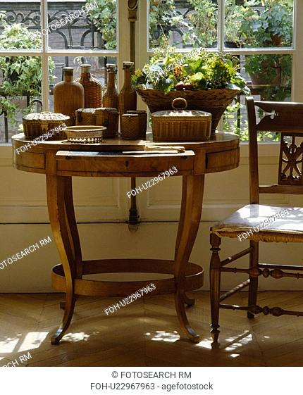Collection of wicker bottles on antique table in front of window in traditional living room