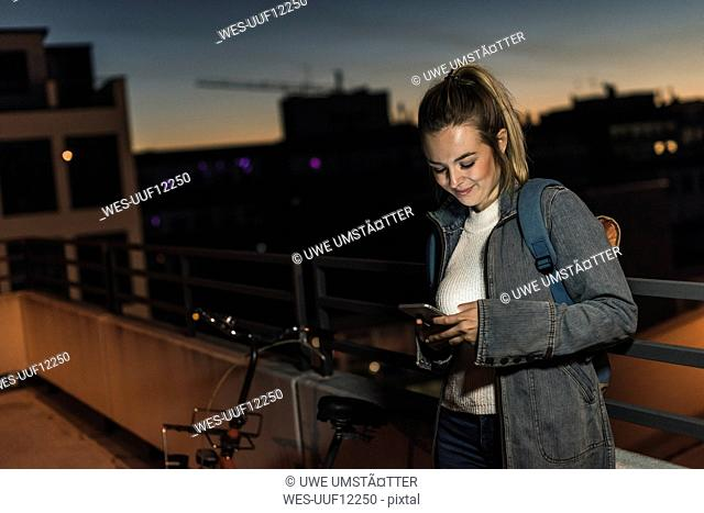 Smiling young woman in the city checking cell phone in the evening
