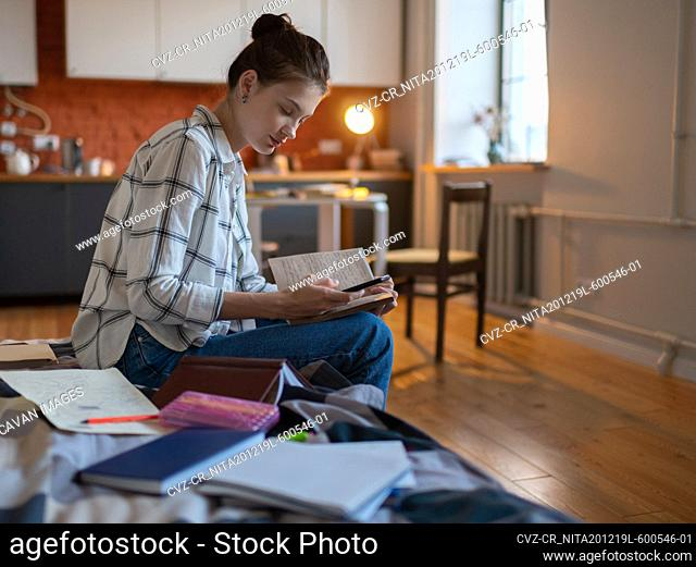 Girl browsing smartphone and taking notes