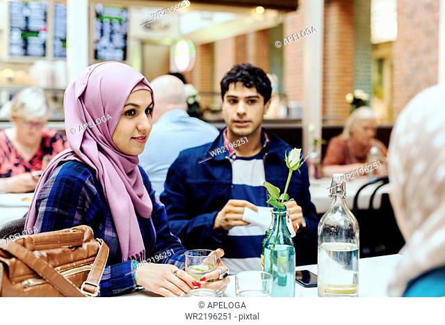 Woman sitting with friends at table in railroad station cafe