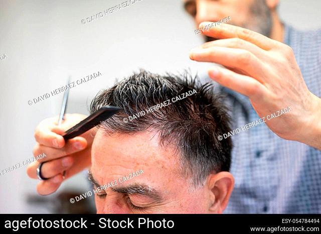 Barber trimming hair of old man at barber shop