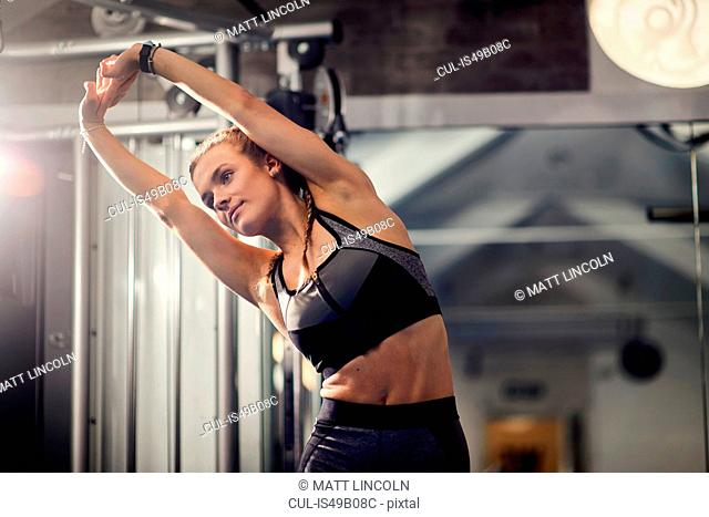 Young woman training, stretching arms in gym
