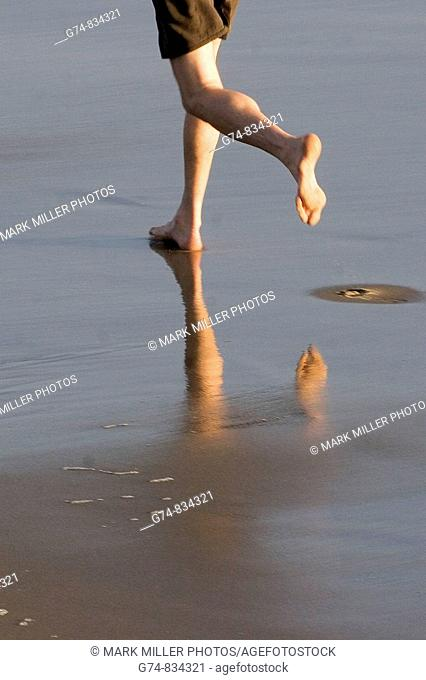 Feet and reflection of a jogger on the California beach