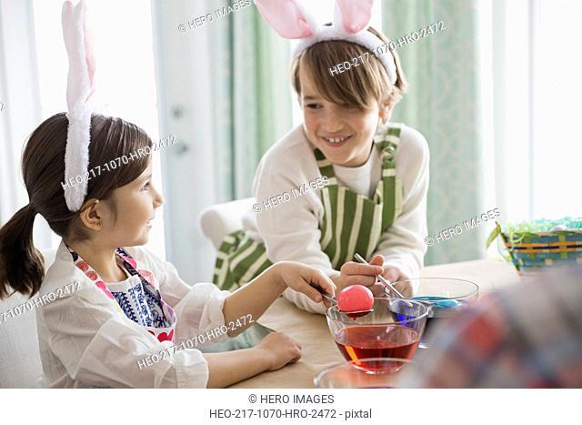 Siblings dyeing Easter eggs
