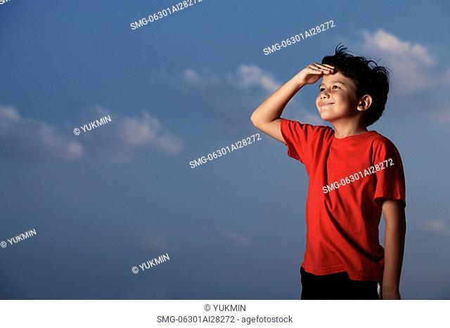 Young boy wearing a red shirt looking out with hand shielding eyes