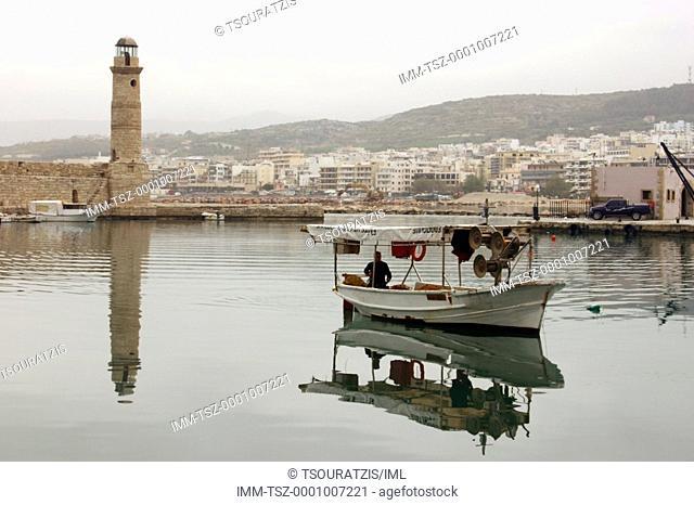 Port, lighthouse, man sitting on fishing boat  Rethymno, Crete, Greece
