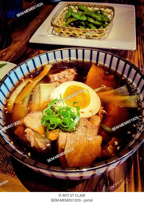 Close up of hot noodle soup with eggs and meat