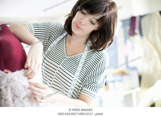 clothing designer pinning material on dress form