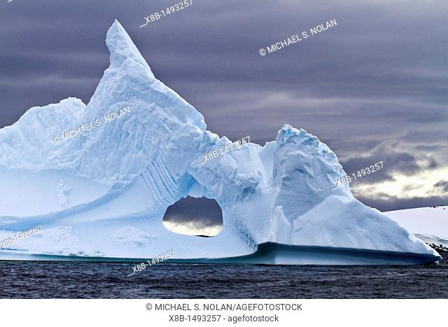 Unusual window formation in iceberg with Booth Island in the background on the western side of the Antarctic Peninsula during the summer months