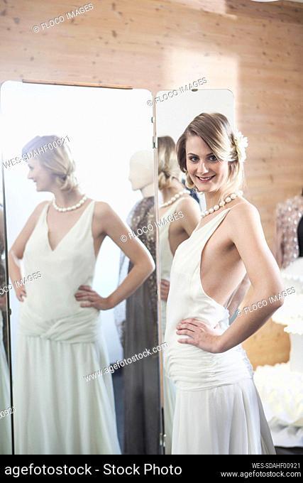 Smiling bride fitting her dress in studio