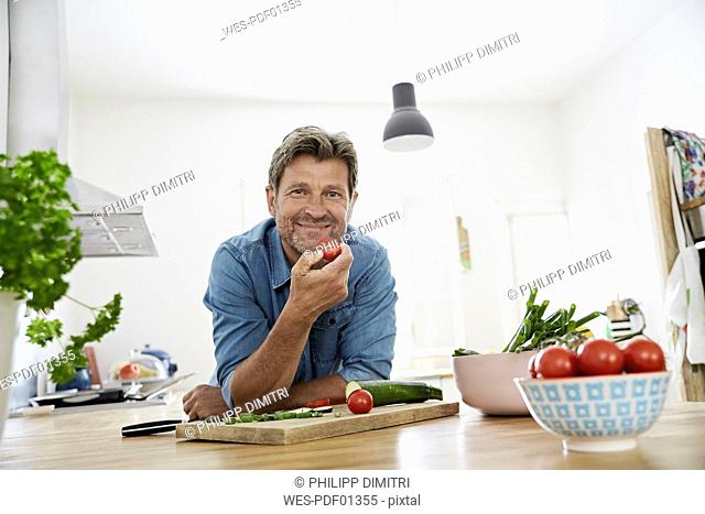 Mature man in his kitchen eating tomato
