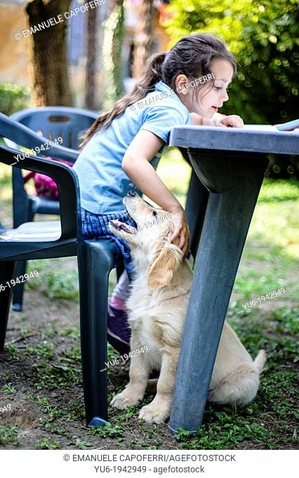 Little girl reads on the table in the garden while caressing a Golden Retriever puppy