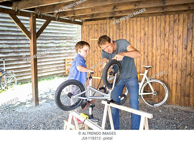 Father And Son Mending Bicycle In Garage At Home