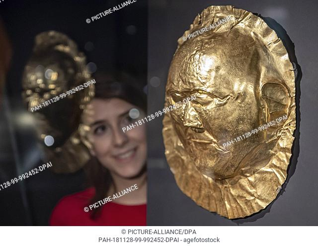 26 November 2018, Baden-Wuerttemberg, Karlsruhe: A person in the Badisches Landesmuseum in Karlsruhe Castle is looking at a golden tomb mask made of Mycenae