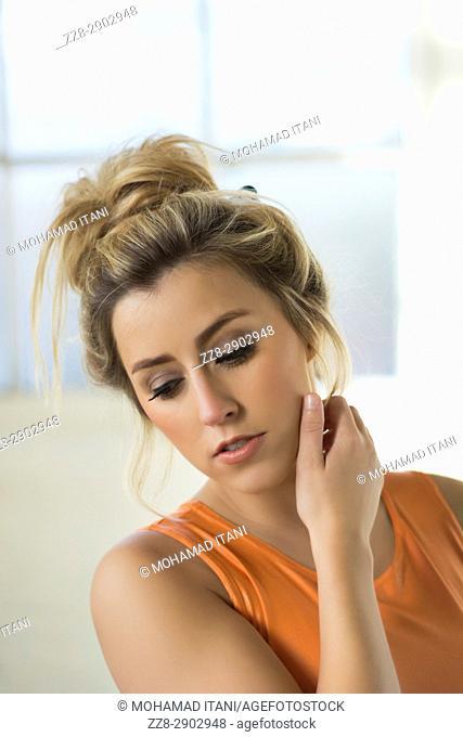 Beautiful young woman hand touching neck