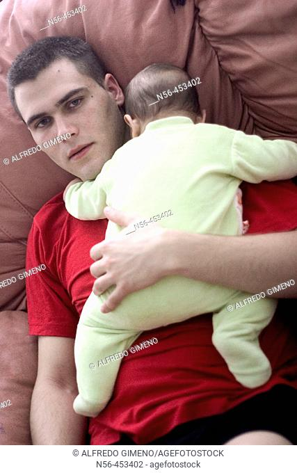 Young man holding baby