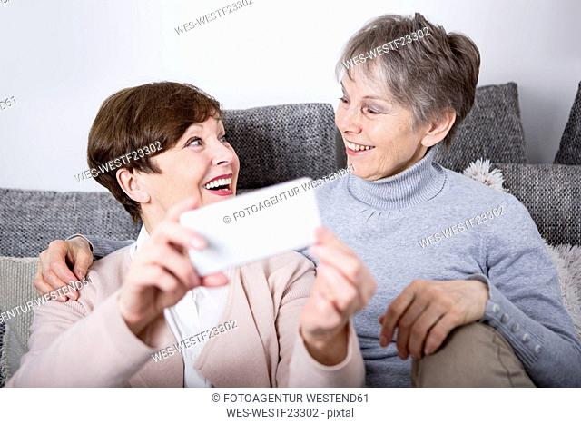 Two senior women sitting on couch