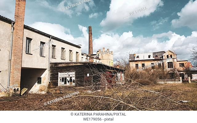 Abandoned old factory building under the blue cloudy sky. Symbol of economic depressions
