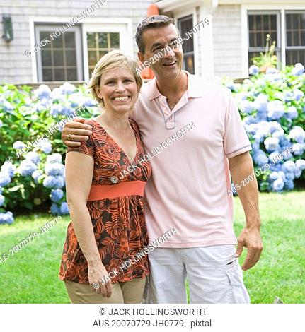 Mature couple standing in a garden with arm around