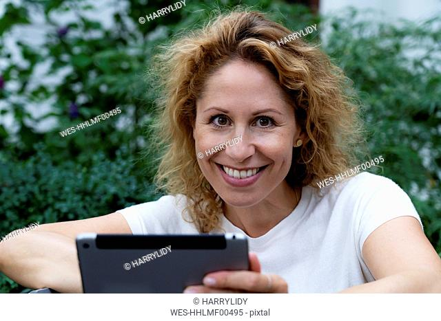 Portrait of smiling woman with digital tablet