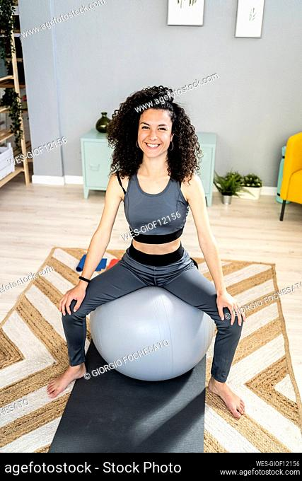 Happy woman sitting on fitness ball in living room