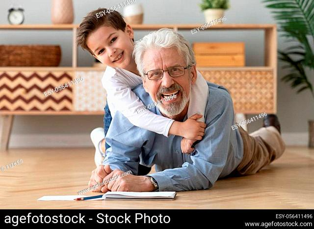 Happy two 2 generations family old grandfather and cute little boy grandson drawing with pencils lying on warm heated wooden floor together