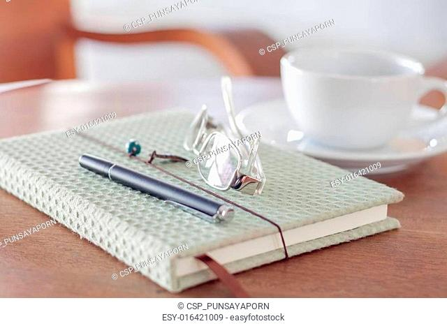 Notebook with pen, eyeglasses and white coffee cup on wooden tab