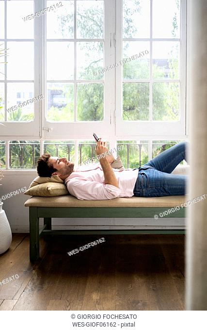 Man lying on bench in front of wondow, using smartphone