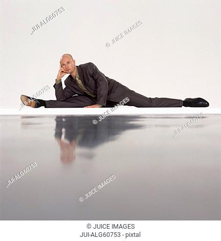 Businessman doing yoga, stretched to one side