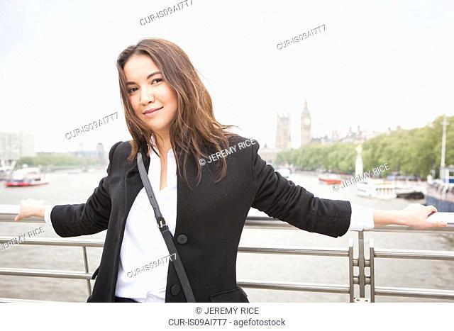 Portrait of young female tourist on Golden Jubilee footbridge, London, UK