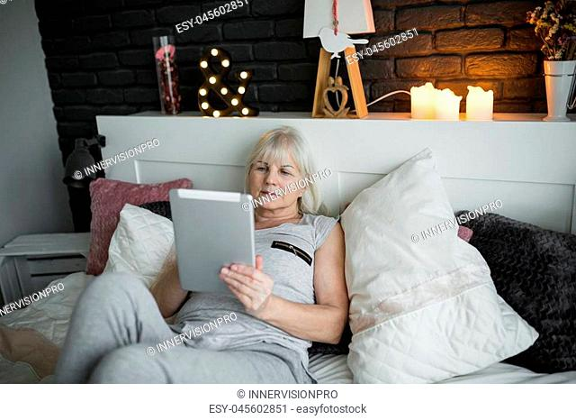 Portrait of senior lady lying on bed reading ebook