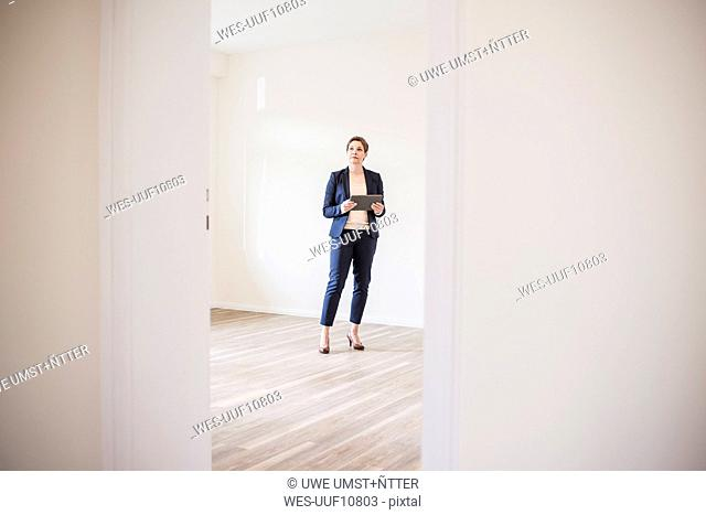 Woman in empty apartment with tablet