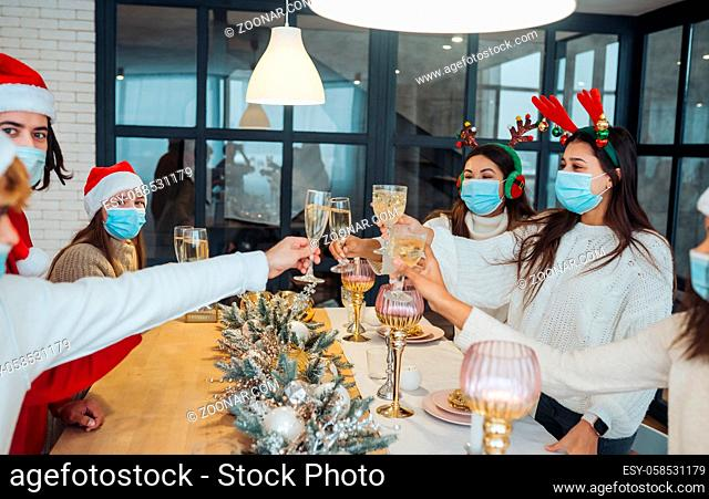 Multi-ethnic young people celebrating New year eve clinking glasses toasting, multiracial friends having fun at party celebration